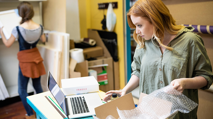 woman at laptop shipping online order in art supply shop