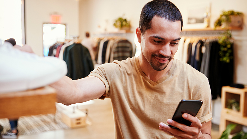 man using smartphone in a clothes shop